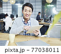 young asian business man sitting at desk in office holding tablet computer looking at camera smiling 77038011