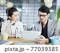 two young asian corporate people discussing business in office using tablet computer 77039385