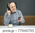 happy man in portable full-size headphones listens to music using a digital player. 77040705