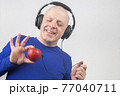 bald man with headphones listens to music through a red apple player.  77040711