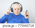 man with headphones and digital portable player in hands in relaxation while listening 77040716