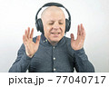 man with closed eyes listens to music with headphones on a light background 77040717