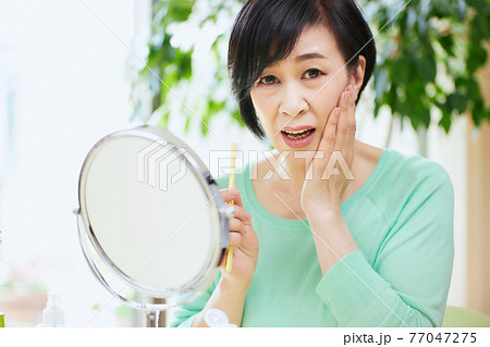 歯ブラシを持つミドル女性 歯痛 77047275