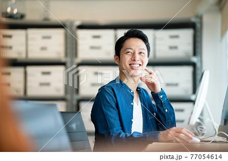 オフィスで仕事をしている男性 77054614