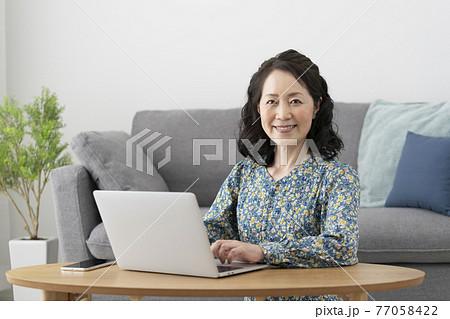 パソコンに向かう笑顔のシニア女性 77058422