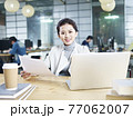 young asian business woman sitting at desk in office holding document looking at camera 77062007