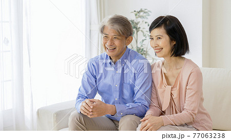 リビングでくつろぐ笑顔の中高年夫婦 77063238