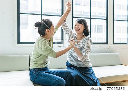 喜びダンスするふたりの女性 77065886