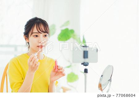 メイク動画を観ながらメイクをする女性 77068604