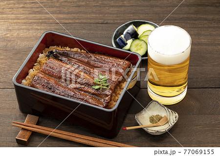 木目のテーブルに置いた照りのある鰻重とビール 77069155