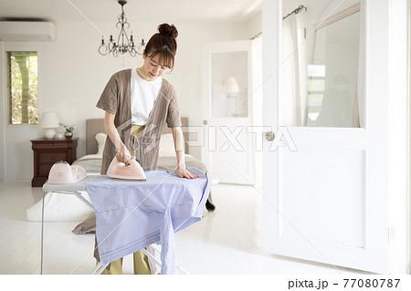 家でアイロンをかける若い女性 77080787