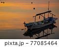 朝凪の瀬戸内の漁港 朝焼けを映す海と浮かぶ漁船 77085464