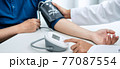 Doctor is checking the patient blood pressure in his hospital office 77087554