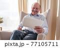 Senior man wathcing photos of his family smiling 77105711