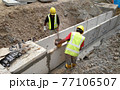 MALACCA, MALAYSIA -JANUARY 31, 2017: Construction workers installing precast u-shape concrete drain at the construction site. The drain was fabricated at the factory and mobilized to site.  77106507