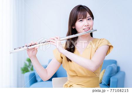 リビングでフルートを吹く女性 77108215