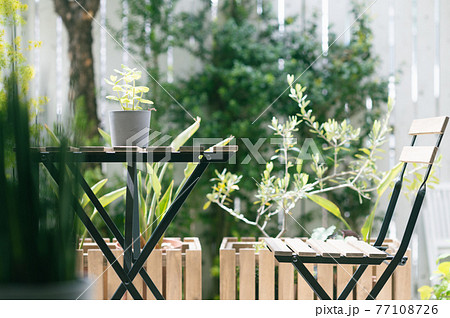 緑豊かなテラスのテーブルと椅子 77108726