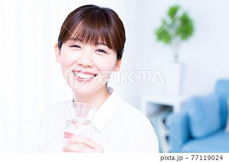 リビングで水を飲む若い女性 77119024