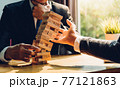 Business man strategy risk pulling block wood tower 77121863