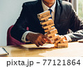 Business man challenge pulling block wood building tower, the block wood has failling on he hand 77121864