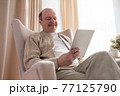 Senior man in sofa with tablet computer at home 77125790