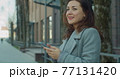 Business woman uses smartphone near business center. Young smiling woman uses a smartphone outdoors. Woman worker. Corporate. Entrepreneur street. 77131420