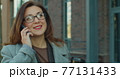 Caucasian young business woman with glasses talking on smartphone with business colleague outside near modern office building. 77131433