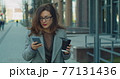 Successful business woman with glasse walking with coffee and uses smartphone in business district. Successful Woman. Phones. Apps. 77131436