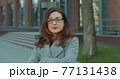Business woman with glasses standing look at camera serious near business center. Corporate people concept. 77131438