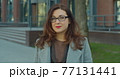 Portrait of beautiful businesswoman with glasses standing outdoor and looking to camera. Corporate woman posing on city street. 77131441