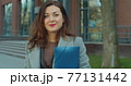 Portrait of beautiful and confident young woman in formal suit standing near modern office building, looking at camera and smiling. 77131442