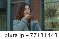 Young successful lady next to corporate office talking on phone. Businesswoman activates smartphone digital virtual voice assistant recording audio messages. 77131443
