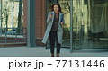 Serious business woman walking with phone near modern office building. Concept: new business, communication, work day, freelancer. 77131446