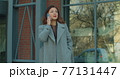Young business woman in a coat is talking on phone outside near modern office building. Serious business woman with phone outdoor. Business, job concept. 77131447