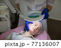 Close up of face of young teen girl with problem skin and acne, lying on the massage table in modern cosmetology clinic. Hands of female doctor beautician in gloves examines the skin of her patient. 77136007