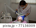 Woman beautician doctor working at modern beauty center. Portrait of a young female professional cosmetologist preparing her teen girl patient to skin treatment procedures. 77136009