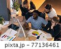 Colleagues working together in modern office using devices and gadgets during creative meeting 77136461