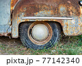Rear wheel of a rusty vintage american car staying on the grass 77142340