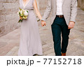 Groom holds the hand of bride in a wedding dress with a bouquet of flowers. Newlyweds stroll along a stone cobblestone 77152718