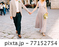 Bride and groom hold hands on the paving stones of the city square 77152754