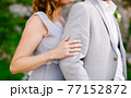 Bride in a gray dress hugs from behind groom in a gray suit 77152872