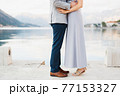 Bride stood on tiptoe in front of groom hugging her against the backdrop of the coast 77153327