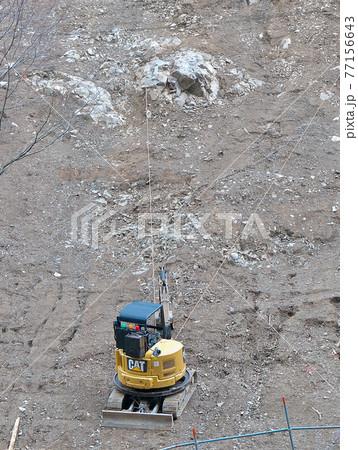 ロープを岩に引っ掛けて支えながら急斜面で作業する小型クレーン 77156643