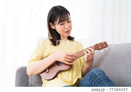 ソファーに座ってウクレレを演奏する女性 77164247