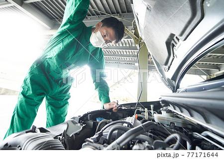 マスクを装着して作業をする自動車整備士 77171644