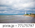 White lighthouse in a bay at sea 77175797