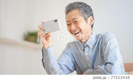 スマートフォンで動画を視聴するシニア男性 77212410