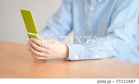 携帯電話を操作するシニア男性 77212887