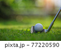 Closeup golf ball on tee ready to be shot. Golf ball on tee in the evening golf course with sunshine. Blurred set of golf clubs over green field background. 77220590