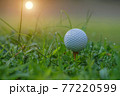 Closeup golf ball on tee ready to be shot. Golf ball on tee in the evening golf course with sunshine. Blurred set of golf clubs over green field background. 77220599